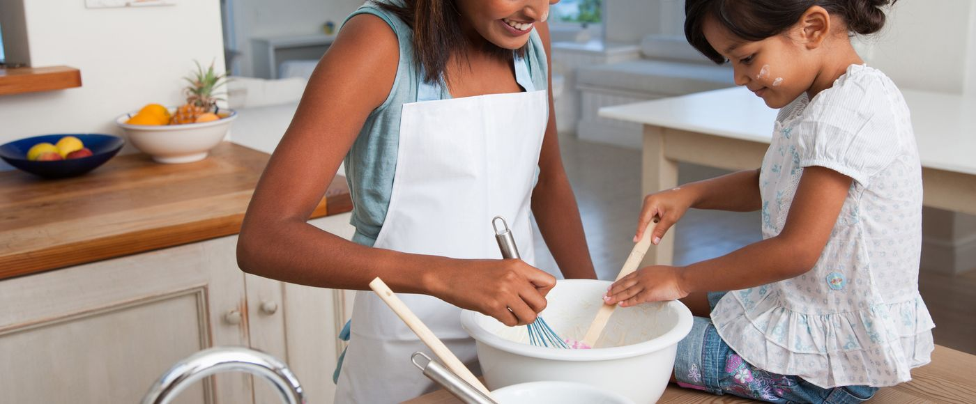 Daughter helping mother mixing batter