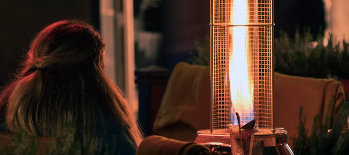 A women sitting by a patio heater on fall night