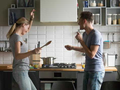 Couple dancing next to stove in kitchen