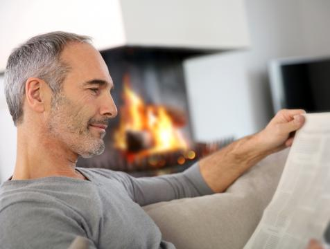 Older man reading the paper by a propane fireplace