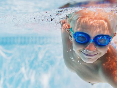 Little boy swimming on a pool with googles