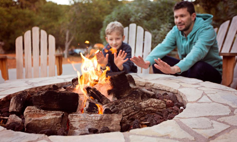 Father and son enjoying an outdoor propane fire pit
