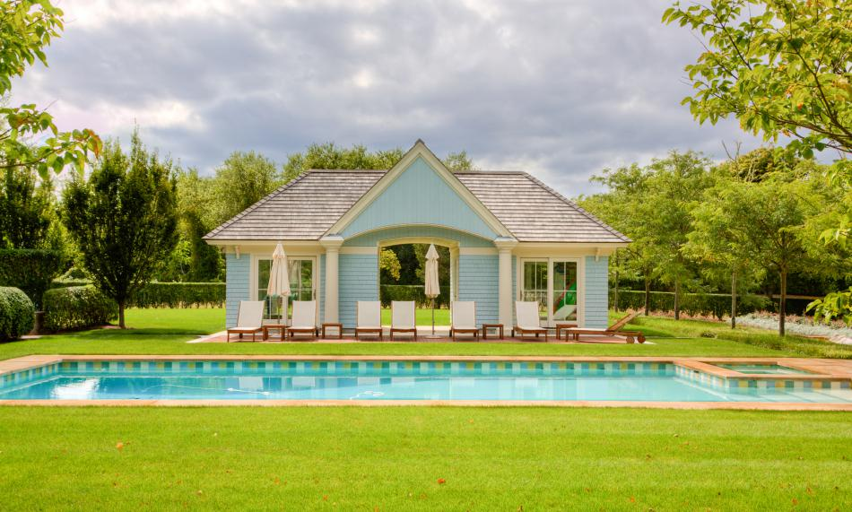 An in-ground pool with a guesthouse