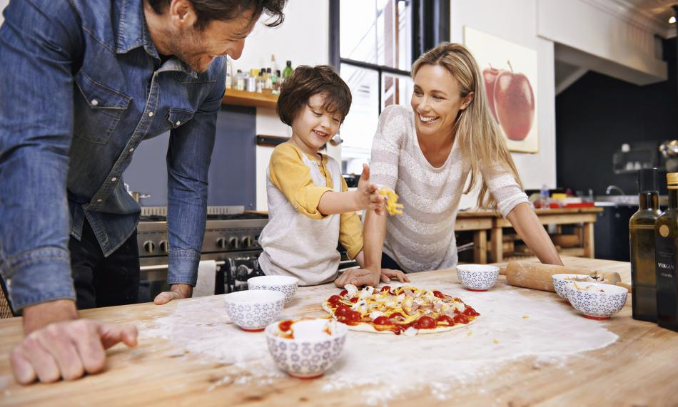 Family making a pizza in the kitchen