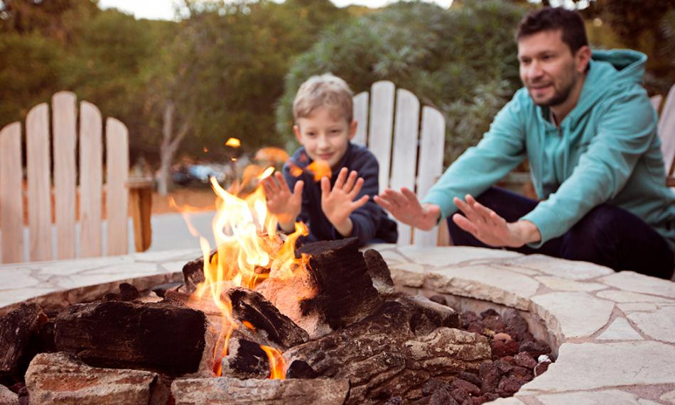 Father and son enjoying an outdoor fireplace