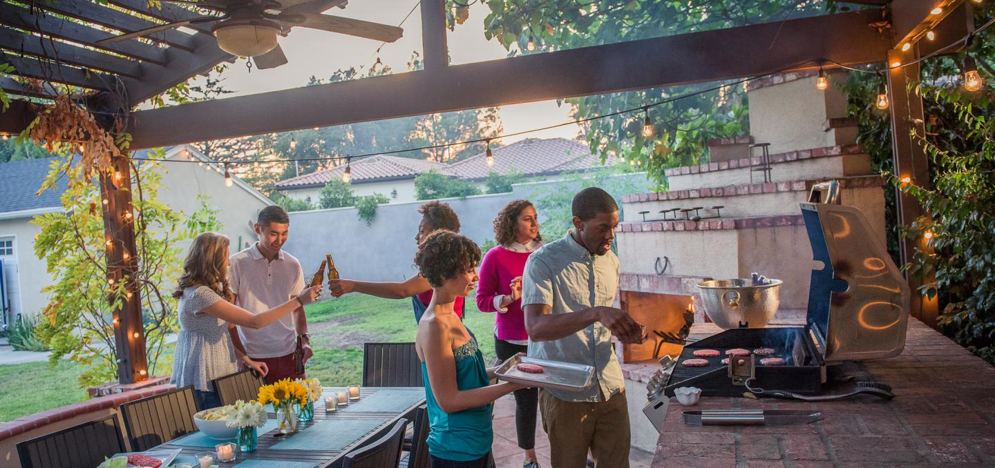 A party with people grilling on an outdoor kitchen