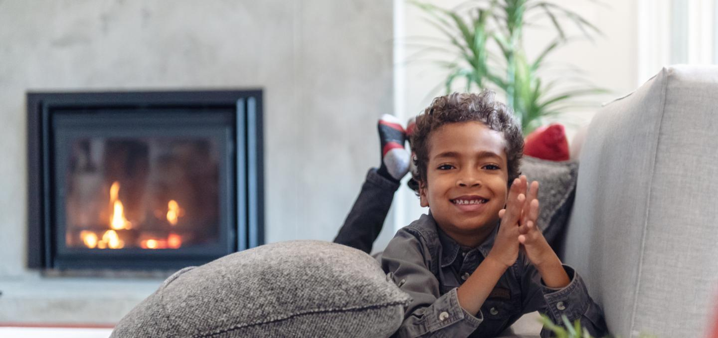 Young boy sitting on the couch by a fireplace