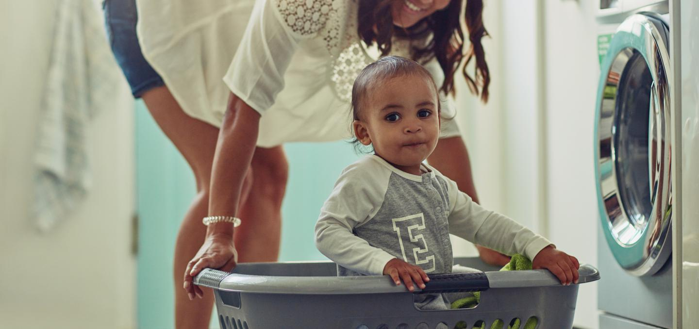 Mother with her toddler doing laundry with propane dryer