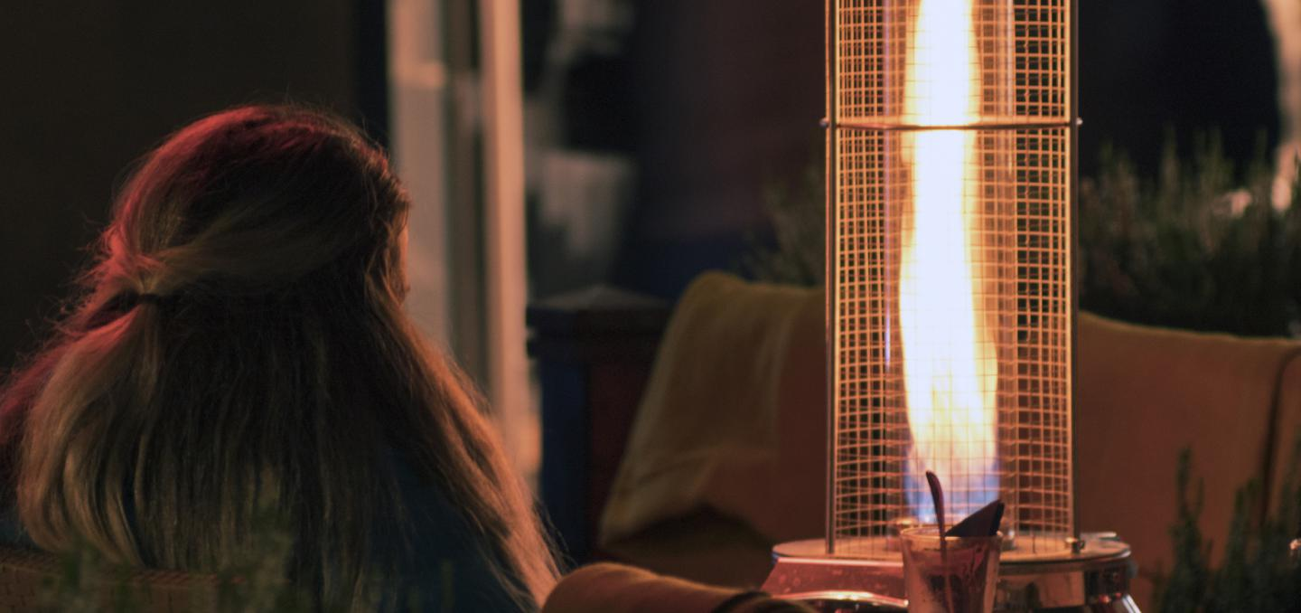 A women sitting by a propane patio heater at night