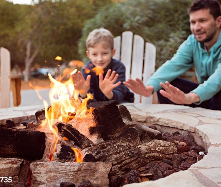 Father and son sitting by an outdoor fire pit on a fall night