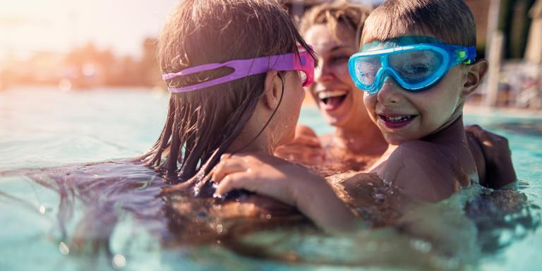 Kids splashing around in a backyard pool