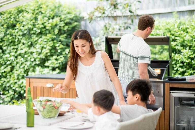 A family eating outside with help from a propane kitchen