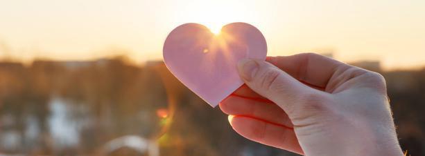 Hand holding a heart shape cut out towards the sun.