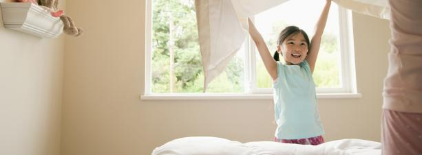 Little girl helping to make the bed with a window in the background