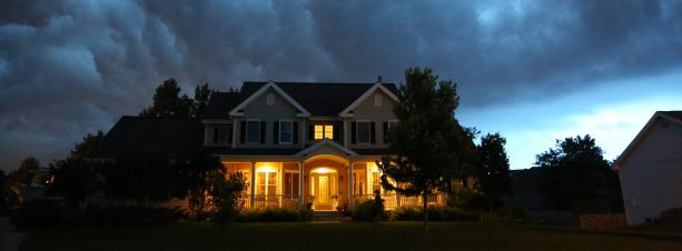 A home with a thunderstorm in the background