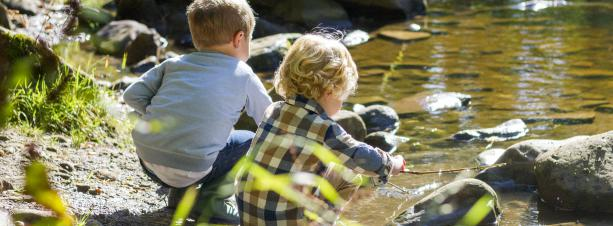 Two boys playing buy a river on a nice summer day