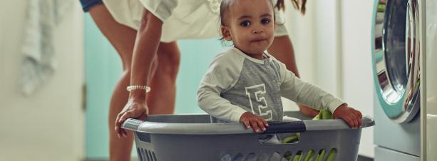 Mother carrier toddler in laundry basket