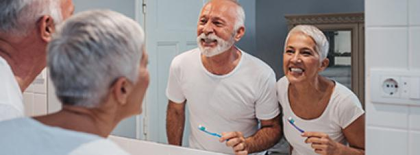 Older couple brushing their teeth in the bathroom