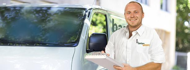 Man holding a clipboard standing next to a van.