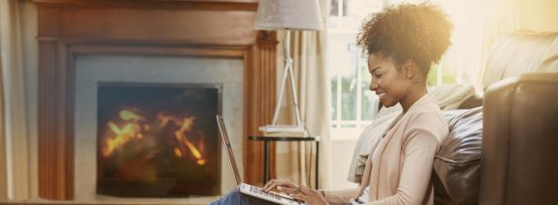 Woman sitting on floor in front of fireplace.