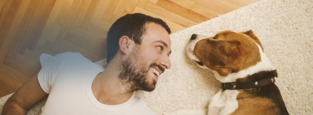 Man and dog relaxing on the floor.