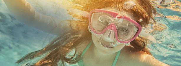 Girl swimming in pool with goggles.