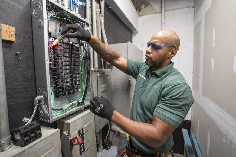 A BantamWesson Electrician working on a fuse box