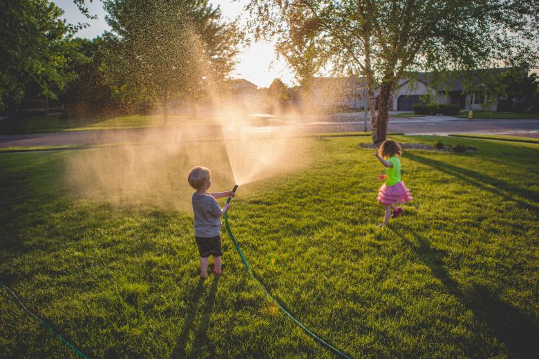 Kids running getting sprayed with hose in the front yard