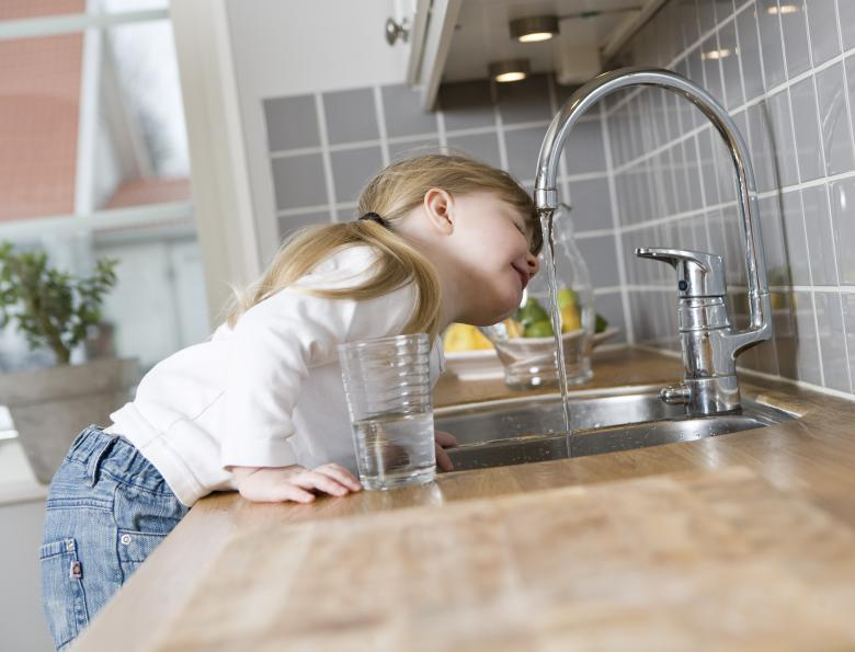 Little girl getting a drink of water from the faucet
