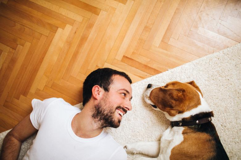 Man and dog lying comfortably on the floor