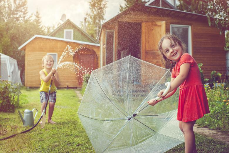 Kids playing in the yard on a rainy day with an umbrella and hose