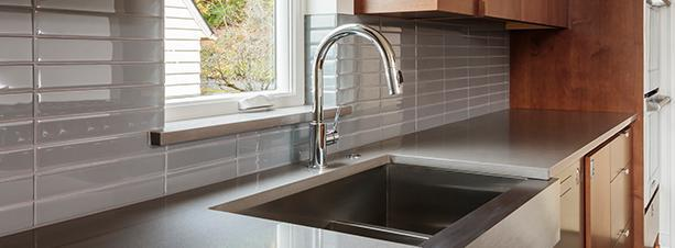 A modern kitchen with an updated sink and faucet
