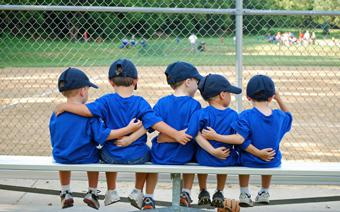 Little League team sitting on a bench.