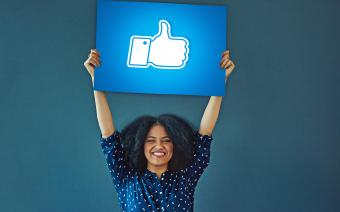 Woman holding up Facebook like sign