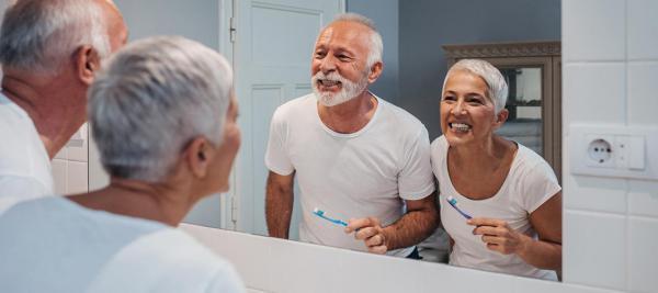 Elderly couple brushing their teeth in the bathroom