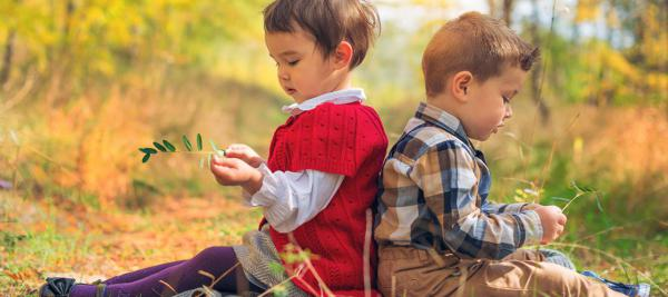 Two young children sitting in the grass holding green leaves