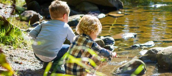 Two children playing near a river