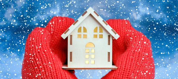Red gloves holding a mock house with snow in the background