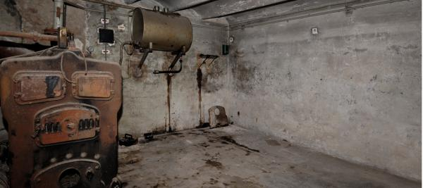 A basement showing an old boiler
