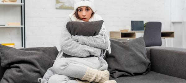 Women sitting on a couch with hat, scarf and boots