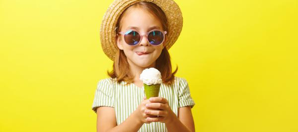 Young girl with sunglasses eating ice cream