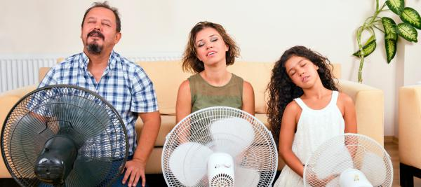 Family sitting in front of fans on a hot summer day