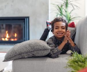Little boy on the couch smiling by a propane fireplace