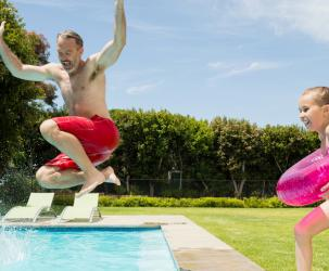 Kids and dad jumping into a pool.