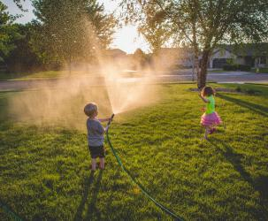 Two kids playing in the yard with a hose